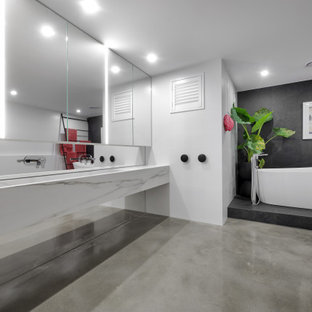 Photo of a large contemporary master bathroom in Perth with white cabinets, a freestanding tub, concrete floors, grey floor, white benchtops, a floating vanity, gray tile, white walls, a trough sink and a double vanity.