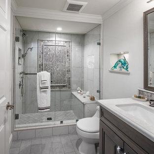 Kleines Klassisches Duschbad mit profilierten Schrankfronten, grauen Schränken, Duschnische, Toilette mit Aufsatzspülkasten, schwarz-weißen Fliesen, Porzellanfliesen, grüner Wandfarbe, Porzellan-Bodenfliesen, Unterbauwaschbecken, Quarzwerkstein-Waschtisch, grauem Boden und Falttür-Duschabtrennung in Orange County