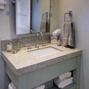 Immagine di una stanza da bagno stile marinaro con lavabo integrato, ante verdi e top in pietra calcarea