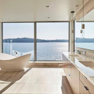 シアトルの大きいコンテンポラリースタイルのおしゃれなマスターバスルーム (フラットパネル扉のキャビネット、中間色木目調キャビネット、置き型浴槽、一体型トイレ、ベージュのタイル、磁器タイル、ベージュの壁、磁器タイルの床、アンダーカウンター洗面器、ライムストーンの洗面台、ベージュの床、ベージュのカウンター) の写真