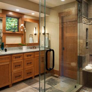 他の地域の大きいおしゃれなマスターバスルーム (シェーカースタイル扉のキャビネット、中間色木目調キャビネット、コーナー設置型シャワー、マルチカラーのタイル、石タイル、ベージュの壁、スレートの床、アンダーカウンター洗面器、御影石の洗面台) の写真