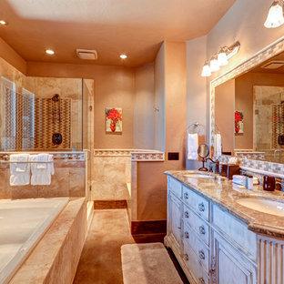 デンバーの中くらいのラスティックスタイルのおしゃれな浴室 (ルーバー扉のキャビネット、ヴィンテージ仕上げキャビネット、ドロップイン型浴槽、コーナー設置型シャワー、分離型トイレ、ベージュのタイル、ライムストーンタイル、ベージュの壁、ライムストーンの床、アンダーカウンター洗面器、御影石の洗面台、マルチカラーの床、開き戸のシャワー、ベージュのカウンター) の写真