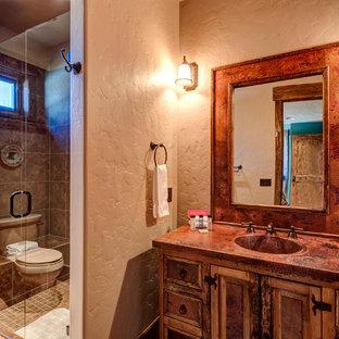 Свежая идея для дизайна: ванная комната среднего размера в стиле рустика с фасадами с филенкой типа жалюзи, искусственно-состаренными фасадами, накладной ванной, угловым душем, раздельным унитазом, бежевой плиткой, коричневой плиткой, плиткой из известняка, бежевыми стенами, полом из известняка, врезной раковиной, разноцветным полом, душем с распашными дверями, столешницей из меди и оранжевой столешницей - отличное фото интерьера