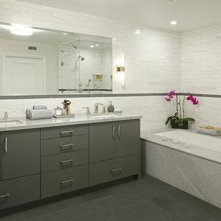 Modelo de cuarto de baño principal, contemporáneo, de tamaño medio, con lavabo bajoencimera, armarios con paneles lisos, puertas de armario grises, bañera encastrada sin remate, ducha esquinera, baldosas y/o azulejos blancos, encimera de mármol, baldosas y/o azulejos de piedra, paredes blancas y suelo gris