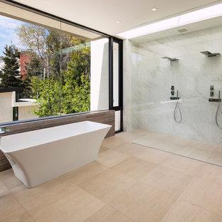 ロサンゼルスの広いコンテンポラリースタイルのおしゃれなマスターバスルーム (置き型浴槽、オープンシャワー、ダブルシャワー、グレーのタイル、石スラブタイル、トラバーチンの床、ベージュの床) の写真