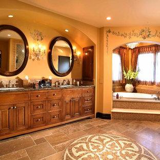 ロサンゼルスの巨大な地中海スタイルのおしゃれなマスターバスルーム (レイズドパネル扉のキャビネット、中間色木目調キャビネット、御影石の洗面台、コーナー型浴槽、茶色いタイル、モザイクタイル、黄色い壁、トラバーチンの床、オーバーカウンターシンク) の写真