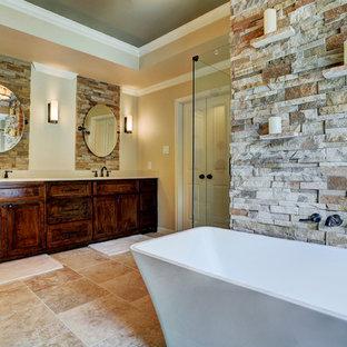 Imagen de cuarto de baño principal, de estilo americano, grande, con lavabo encastrado, armarios con paneles empotrados, puertas de armario de madera en tonos medios, encimera de mármol, bañera exenta, ducha abierta, baldosas y/o azulejos beige, baldosas y/o azulejos de piedra, paredes beige y suelo de travertino