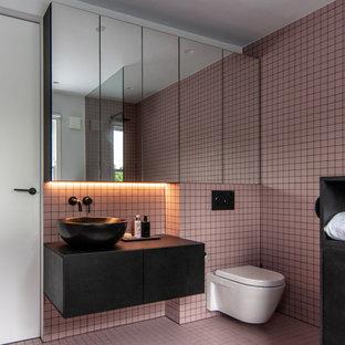 Idéer för att renovera ett mellanstort funkis svart svart badrum, med släta luckor, svarta skåp, en vägghängd toalettstol, rosa kakel, rosa väggar, rosa golv och ett fristående handfat