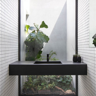 Design ideas for an industrial bathroom in Sydney with white tile, mosaic tile, an integrated sink, white floor and black benchtops.