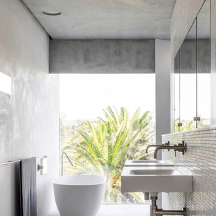 Photo of an industrial bathroom in Sydney with a freestanding tub, white tile, mosaic tile, white walls, mosaic tile floors, a wall-mount sink and white floor.