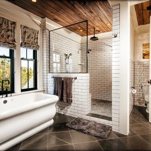 Großes Klassisches Badezimmer En Suite mit freistehender Badewanne, weißen Fliesen, Metrofliesen, Porzellan-Bodenfliesen, Eckdusche, Wandtoilette mit Spülkasten, offener Dusche, verzierten Schränken, hellen Holzschränken, weißer Wandfarbe, Waschtischkonsole und grauem Boden in Charleston