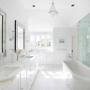 Bathroom - transitional master bathroom idea in New York with white cabinets, white walls, an undermount sink and a hinged shower door