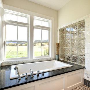 他の地域の中くらいのトランジショナルスタイルのおしゃれなマスターバスルーム (ドロップイン型浴槽、アルコーブ型シャワー、亜鉛の洗面台、白い壁、モザイクタイル、シェーカースタイル扉のキャビネット、白いキャビネット、白いタイル、大理石タイル、マルチカラーの床、開き戸のシャワー) の写真