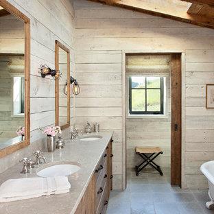 Imagen de cuarto de baño principal, rústico, con puertas de armario de madera oscura, bañera con patas, lavabo bajoencimera y suelo gris