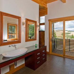 Ejemplo de cuarto de baño principal, rural, grande, con lavabo sobreencimera, armarios con paneles lisos, puertas de armario de madera en tonos medios, encimera de vidrio, paredes blancas y suelo de baldosas de cerámica