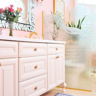 タンパの中くらいのトラディショナルスタイルのおしゃれなマスターバスルーム (家具調キャビネット、白いキャビネット、猫足バスタブ、ピンクの壁、アンダーカウンター洗面器、珪岩の洗面台) の写真