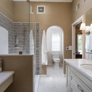 Diseño de cuarto de baño principal, clásico, de tamaño medio, con puertas de armario blancas, sanitario de una pieza, baldosas y/o azulejos grises, baldosas y/o azulejos de vidrio, lavabo bajoencimera, encimera de cuarzo compacto, suelo blanco, ducha con puerta con bisagras, encimeras blancas, armarios con rebordes decorativos y paredes marrones