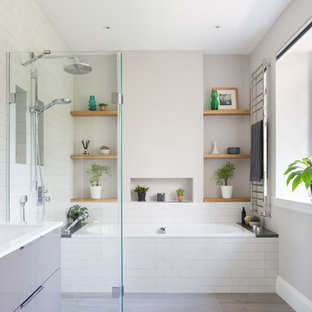 Inspiration for a medium sized contemporary wet room in Other with flat-panel cabinets, a built-in bath, white tiles, metro tiles, grey walls, laminate floors, a wall-mounted sink, grey floors and an open shower.