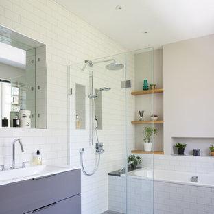 Imagen de cuarto de baño contemporáneo, de tamaño medio, sin sin inodoro, con armarios con paneles lisos, bañera encastrada, baldosas y/o azulejos blancos, baldosas y/o azulejos de cemento, paredes grises, suelo laminado, lavabo suspendido, suelo gris y ducha abierta