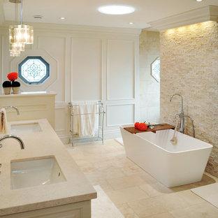 Idée de décoration pour une grande salle de bain principale tradition avec un lavabo encastré, un placard avec porte à panneau encastré, un plan de toilette en marbre et une baignoire indépendante.