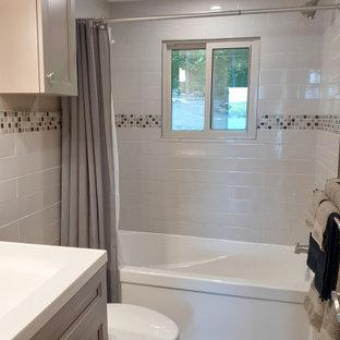 Kleines Modernes Badezimmer En Suite mit Schrankfronten im Shaker-Stil, grauen Schränken, Duschbadewanne, Toilette mit Aufsatzspülkasten, grauen Fliesen, Keramikfliesen, grauer Wandfarbe, Vinylboden, Einbauwaschbecken, Marmor-Waschbecken/Waschtisch, grauem Boden, Duschvorhang-Duschabtrennung, weißer Waschtischplatte, Einzelwaschbecken und freistehendem Waschtisch in Sonstige