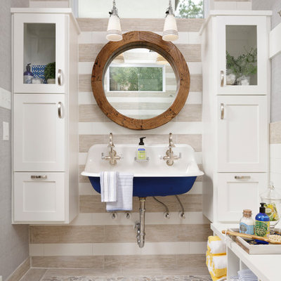 Inspiration for a mid-sized coastal 3/4 beige tile pebble tile floor and beige floor bathroom remodel in Houston with a wall-mount sink, shaker cabinets, white cabinets, gray walls and white countertops
