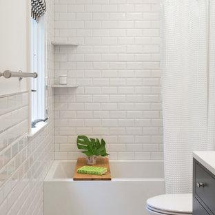 Foto på ett litet lantligt badrum för barn, med släta luckor, grå skåp, ett badkar i en alkov, en dusch/badkar-kombination, en toalettstol med separat cisternkåpa, vit kakel, keramikplattor, vita väggar, klinkergolv i porslin, ett undermonterad handfat och bänkskiva i akrylsten