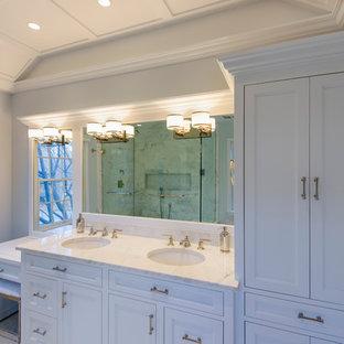 Modelo de cuarto de baño principal, actual, de tamaño medio, con armarios con rebordes decorativos, puertas de armario blancas, ducha esquinera, paredes azules, suelo de baldosas de cerámica, lavabo encastrado, encimera de granito, sanitario de una pieza, baldosas y/o azulejos grises, baldosas y/o azulejos blancos y baldosas y/o azulejos de piedra