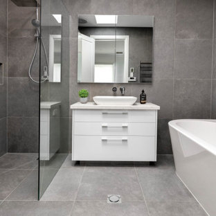 Photo of a large contemporary kids bathroom in Melbourne with flat-panel cabinets, white cabinets, a freestanding tub, gray tile, porcelain tile, porcelain floors, a vessel sink, grey floor, an open shower, white benchtops, a niche, a single vanity, a built-in vanity, an open shower, grey walls and engineered quartz benchtops.