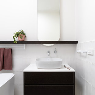 Design ideas for a contemporary bathroom in Melbourne with flat-panel cabinets, black cabinets, a freestanding tub, white tile, white walls, a vessel sink, white floor, white benchtops, a single vanity and a floating vanity.