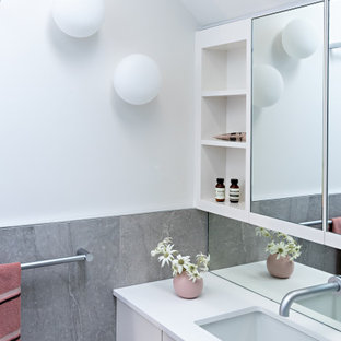 Photo of a contemporary bathroom in Melbourne with flat-panel cabinets, white cabinets, white walls, an undermount sink, white benchtops, a single vanity, a floating vanity and vaulted.