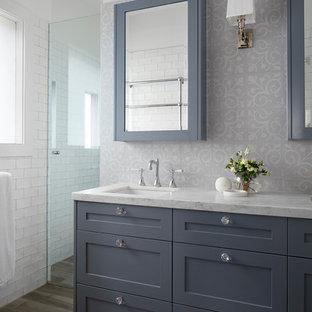 Klassisk inredning av ett mellanstort vit vitt badrum med dusch, med möbel-liknande, grå skåp, ett fristående badkar, en hörndusch, flerfärgad kakel, tunnelbanekakel, vita väggar, plywoodgolv, ett integrerad handfat, marmorbänkskiva, brunt golv och med dusch som är öppen