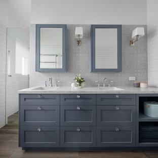 Foto på ett mellanstort vintage vit badrum med dusch, med möbel-liknande, grå skåp, ett fristående badkar, en hörndusch, flerfärgad kakel, tunnelbanekakel, vita väggar, plywoodgolv, ett integrerad handfat, marmorbänkskiva, brunt golv och med dusch som är öppen