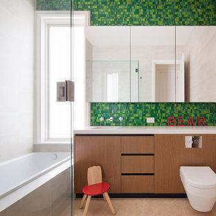 Foto på ett funkis badrum för barn, med en vägghängd toalettstol, grön kakel och mosaik