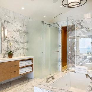 Ispirazione per un'ampia stanza da bagno padronale design con ante lisce, piastrelle di marmo, pavimento in marmo, lavabo sottopiano, top bianco, ante in legno chiaro, vasca freestanding, doccia doppia, piastrelle bianche, pareti bianche, top in marmo, pavimento bianco e porta doccia scorrevole