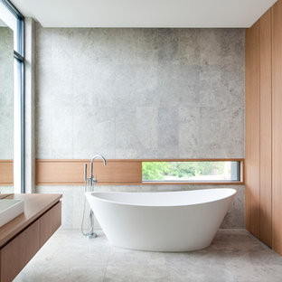 Design ideas for a modern bathroom in Melbourne with flat-panel cabinets, medium wood cabinets, a freestanding tub, grey walls, a vessel sink, wood benchtops, grey floor and brown benchtops.