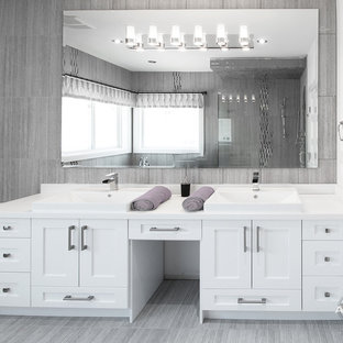 Diseño de cuarto de baño principal, moderno, grande, con lavabo bajoencimera, armarios estilo shaker, puertas de armario blancas, encimera de mármol, bañera esquinera, sanitario de una pieza, baldosas y/o azulejos grises, azulejos en listel, paredes blancas, suelo de madera clara y ducha esquinera