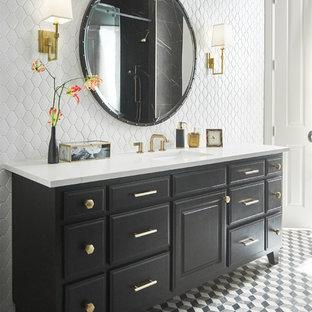 Imagen de cuarto de baño principal, clásico renovado, de tamaño medio, con armarios con paneles empotrados, puertas de armario negras, baldosas y/o azulejos negros, baldosas y/o azulejos de mármol, paredes amarillas, suelo con mosaicos de baldosas, lavabo bajoencimera, encimera de cuarcita, suelo negro, ducha con puerta corredera y encimeras blancas