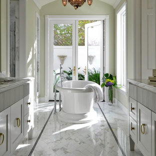 Example of a transitional mosaic tile and white tile marble floor freestanding bathtub design in New York with recessed-panel cabinets and white cabinets