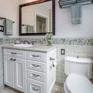 Inspiration pour une petit salle d'eau traditionnelle avec des portes de placard blanches, un carrelage multicolore, un carrelage gris, un carrelage en pâte de verre, un mur blanc, un placard avec porte à panneau encastré, un lavabo posé et un plan de toilette gris.