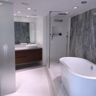 Mittelgroßes Modernes Badezimmer En Suite mit freistehender Badewanne, Eckdusche, grauen Fliesen, Steinplatten, weißer Wandfarbe, Aufsatzwaschbecken, weißem Boden, offener Dusche, Beton-Waschbecken/Waschtisch, flächenbündigen Schrankfronten und hellbraunen Holzschränken in Miami