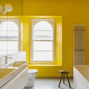 Exempel på ett modernt badrum, med släta luckor, vita skåp, ett fristående badkar, en toalettstol med hel cisternkåpa, vit kakel, gula väggar, ett konsol handfat och grått golv