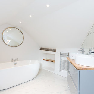 Contemporary ensuite bathroom in London with flat-panel cabinets, grey cabinets, a freestanding bath, white walls, a vessel sink, wooden worktops, white floors and brown worktops.