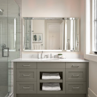 This is an example of a transitional kids bathroom in Calgary with recessed-panel cabinets, grey cabinets, an alcove shower, a one-piece toilet, white walls, porcelain floors, an undermount sink, engineered quartz benchtops, white floor, a hinged shower door, yellow benchtops and stone slab.