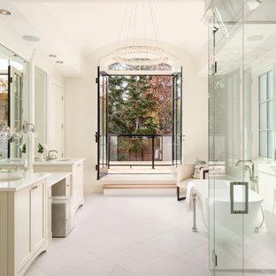 Пример оригинального дизайна интерьера: главная ванная комната в стиле современная классика с фасадами с утопленной филенкой, бежевыми фасадами, отдельно стоящей ванной, душем без бортиков, унитазом-моноблоком, плиткой из листового стекла, белыми стенами, полом из керамогранита, врезной раковиной, столешницей из искусственного кварца, белым полом, душем с распашными дверями и желтой столешницей