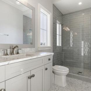 Ispirazione per una stanza da bagno con doccia stile marino di medie dimensioni con ante in stile shaker, ante grigie, doccia alcova, WC monopezzo, piastrelle diamantate, pareti grigie, lavabo sottopiano, top in marmo, pavimento grigio, porta doccia a battente, top bianco e pavimento con piastrelle a mosaico