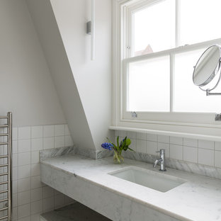 Photo of a traditional bathroom in London with flat-panel cabinets, white cabinets, white tiles, grey walls, mosaic tile flooring, a submerged sink, marble worktops, white floors and white worktops.