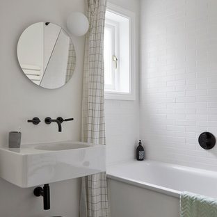 Small contemporary family bathroom in London with a built-in bath, white tiles, ceramic tiles, white walls, ceramic flooring, a wall-mounted sink, marble worktops, black floors, white worktops and a built-in shower.