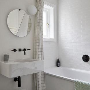 Ispirazione per una piccola stanza da bagno per bambini minimal con vasca da incasso, piastrelle bianche, piastrelle in ceramica, pareti bianche, pavimento con piastrelle in ceramica, lavabo sospeso, top in marmo, pavimento nero, top bianco e doccia a filo pavimento
