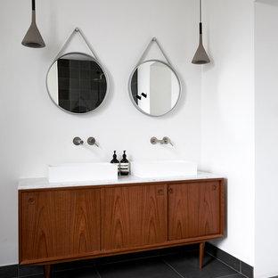На фото: большая главная ванная комната в скандинавском стиле с отдельно стоящей ванной, открытым душем, белыми стенами, полом из керамической плитки, настольной раковиной, мраморной столешницей, черным полом, открытым душем, белой столешницей, плоскими фасадами и коричневыми фасадами с